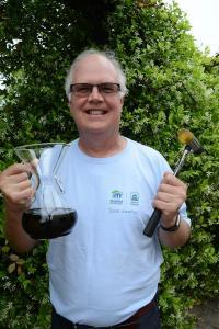 Bill Harris in his Habitat for Humanity shirt, holding a carafe of Chemex-brewed coffee and a hammer.
