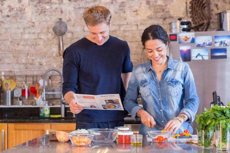 A couple follows a PeachDish recipe, cutting tomatoes and preparing other vegetables to cook for a meal.