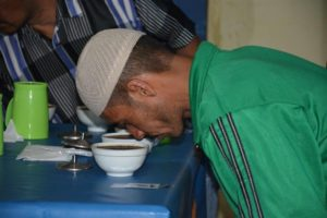 Co-op member smells Sumatran coffee during a Cooperative Coffees-led cupping workshop there.