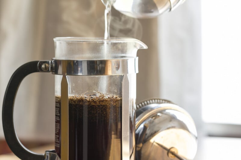 Hot water pouring over coffee grounds in a French Press